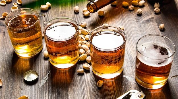 나무 테이블에 피스타치오와 4 개의 맥주