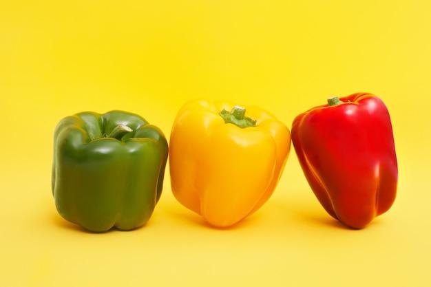 黄色の背景に赤、オレンジ、緑、黄色の4つのピーマン、