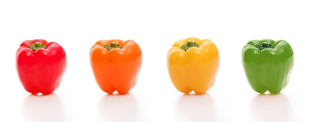 Four bell peppers, red, orange, green and yellow on white background,