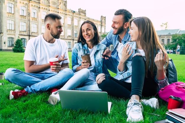 大学の領土の芝生の上にラップトップを持っている4人の最高の若い学生の友人は幸せで興奮しています