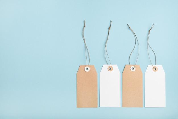 Четыре чистых бумажных ценника с завязанными нитями на синем столе