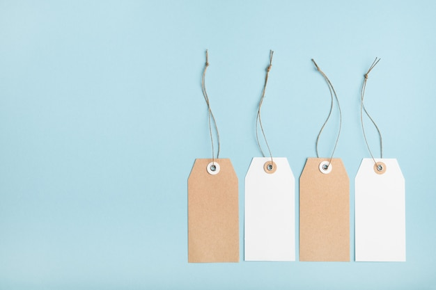Four blank paper price tag with a knotted string on a blue table