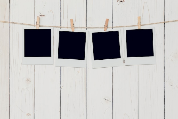 Four blank photo frame hanging on white wood background with space