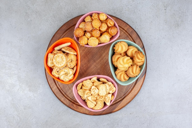 Quattro ciotole di biscotti e patatine su tavola di legno su superficie di marmo.