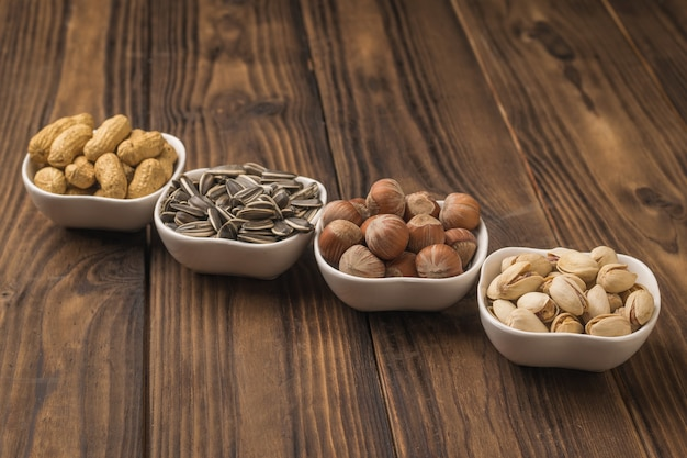 Four bowls of nuts and seeds were neatly arranged on a wooden table. a mixture of nuts and seeds.