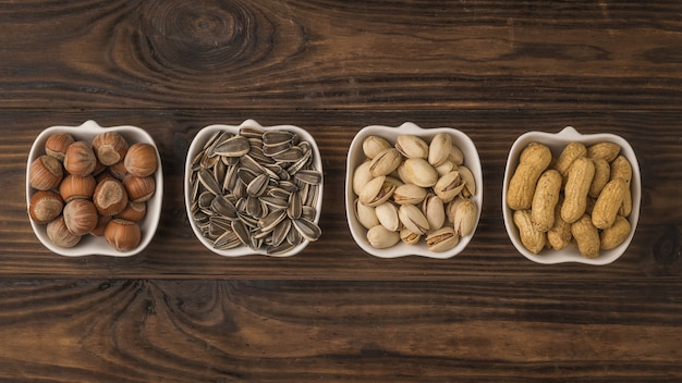 Four bowls of popular nuts and seeds on a wooden table. a mixture of nuts and seeds. the view from the top.