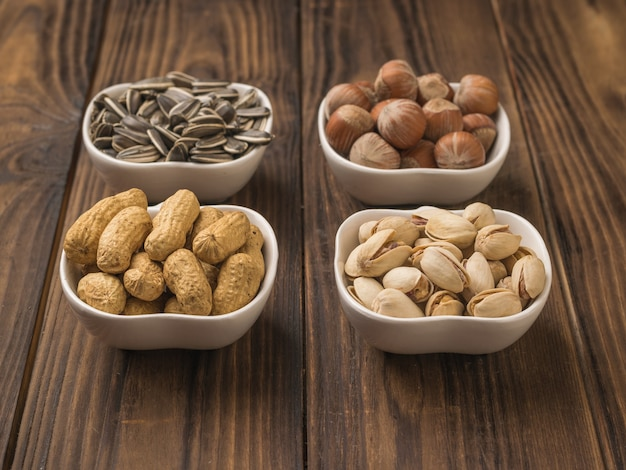 Four bowls of popular nuts and seeds on a wooden table. a mixture of nuts and seeds.