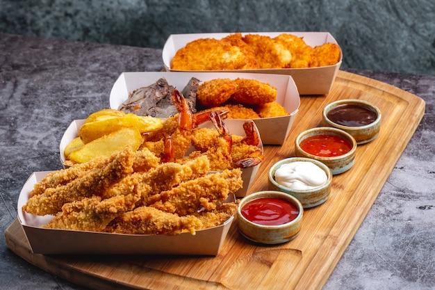 Quattro scatole di pepite di pollo con gamberi e pesce con quattro salse