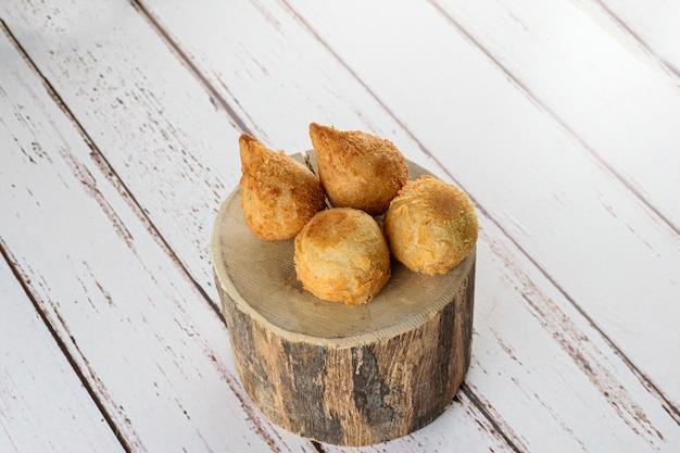 Четыре бразильских закуски, обжаренные в масле с сырно-куриной начинкой.