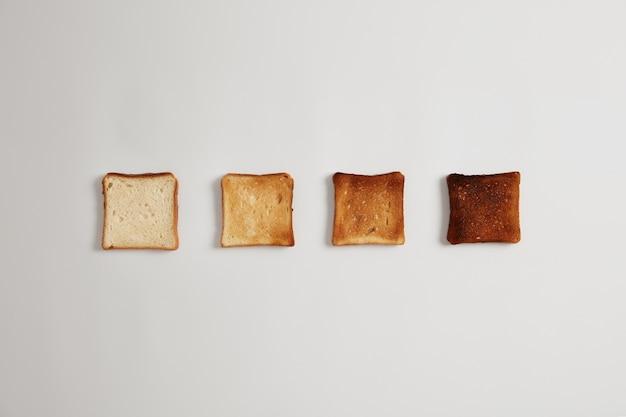 토스터에서 구운 것부터 구운 것까지 4 개의 빵 조각이 흰색 표면에 나란히 배열되어 있습니다. 맛있는 피 각질의 샌드위치를 만들기위한 토스트 빵 조각 세트. 맛있는 아침 식사, 요리 음식