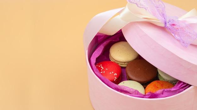 桃の背景にピンクの段ボール箱に4つの鮮やかな色のフレンチマカロン空きスペース