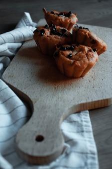 Четыре коричневых кекса на коричневой деревянной разделочной доске