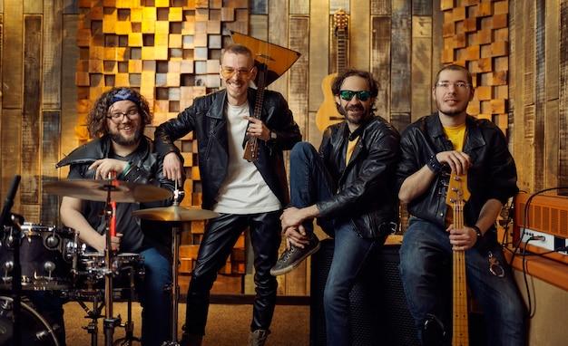 4人の残忍なアーティストがステージでポーズをとります。ガレージでのロックバンドの演奏やコンサートの繰り返し、楽器を持った男、ライブサウンドパフォーマー