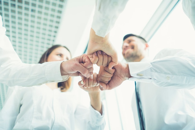 The four business people gesture with a fist