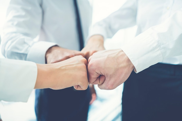 The four business people greeting with a fist