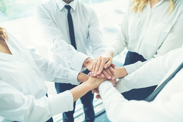 The four business people hold hands together