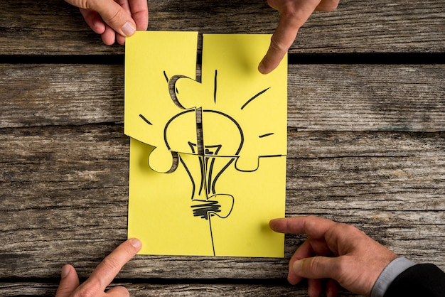 Four business people holding pieces of a jigsaw puzzle bearing the image of a light bulb conceptual of brainstorming or teamwork.