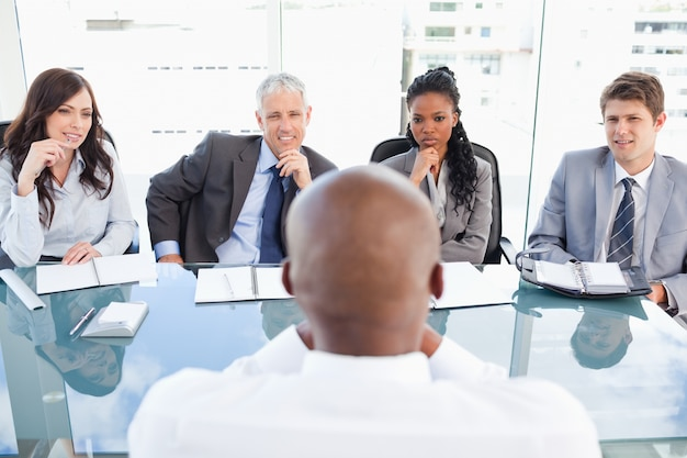 Four business people sitting at the desk while attentively listening to explanations
