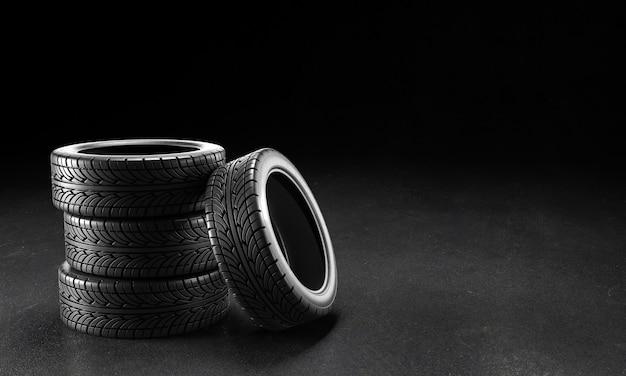 黒の背景のアスファルトに4つの車のタイヤ。 3dレンダリング