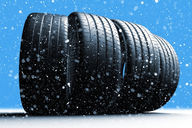 Four car tires rolling on a snow covered road