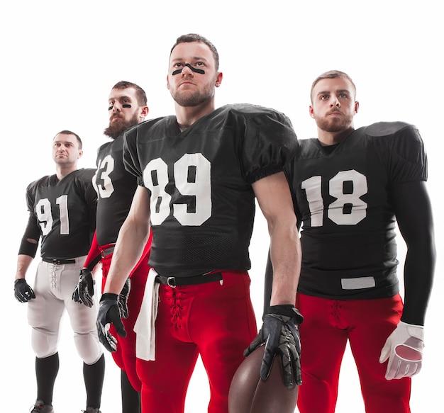 I quattro uomini caucasici di fitness come giocatori di football americano in posa a figura intera con una palla su sfondo bianco