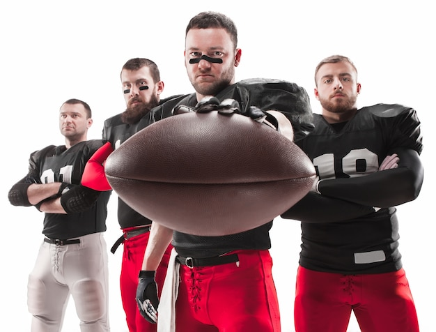 The four caucasian fitness men as american football players posing  full-length with a ball on white