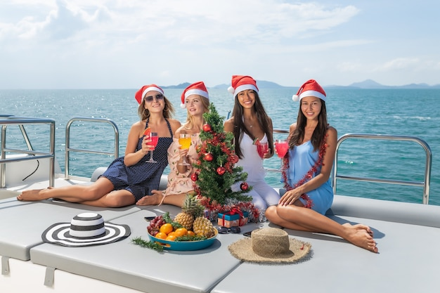 Four caucasian girlfriends have a christmas party on a yacht