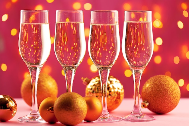 Four champagne glasses against blurred garland lights