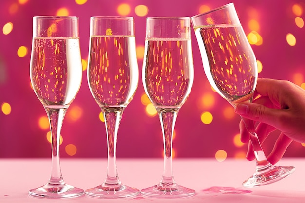 Four champagne glasses against pink background with blurred garland lights