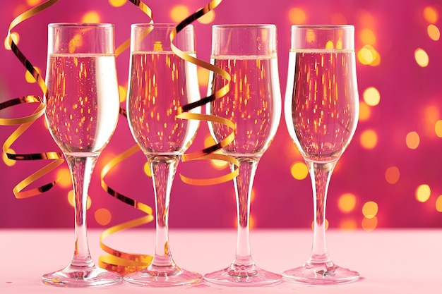 Four champagne glasses against pink background with blurred garland