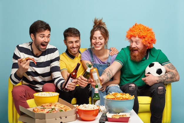 Four cheerful friends clink bottles of beer, have spare time together, watch football match or broadcast of sport event on tv at home, have popcorn, pizza and chips on table, cheer for favorite team