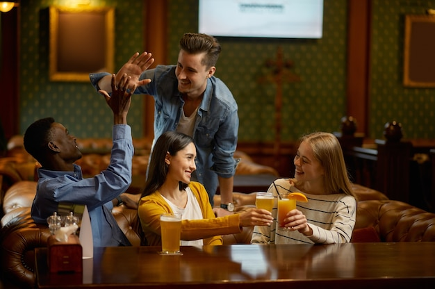 4 명의 쾌활한 친구가 바 카운터에서 술을 마신다.