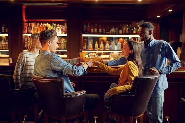 Four cheerful friends drinks beer at the counter in bar. group of people relax in pub, night lifestyle, friendship, event celebration
