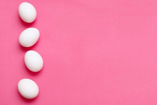 Четыре куриных яйца на ярко-розовой поверхности