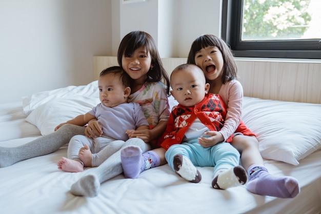 Четверо детей с удовольствием играют и шутят в постели