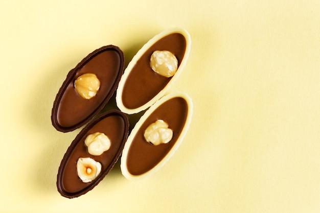 Четыре шоколадные конфеты с орехами на желтом фоне, вид сверху