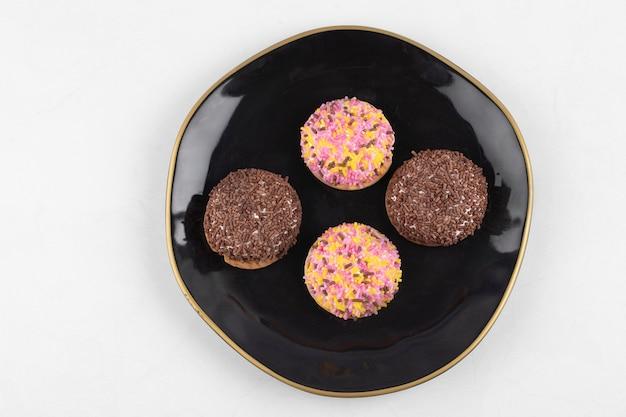 Четыре кружка зефира из печенья с красочными брызгами на черной тарелке