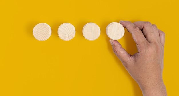 4つの円形の木製ブロックが黄色の背景に配置され、手が最後の木製ブロックを拾っています。ウッドブロックのコンセプト、テキスト、ポスター、モックアップテンプレートのコピースペースのバナー。