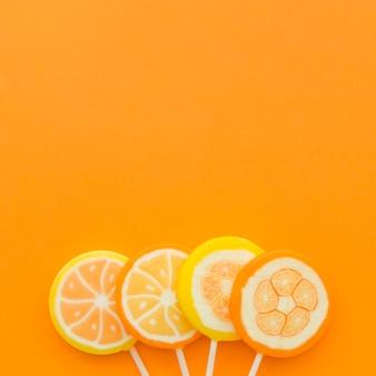 Four citrus fruit lollipops at the bottom of orange backdrop