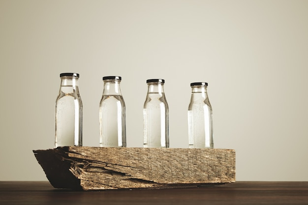 Four clear transparent glass bottles with black caps filled with pure drinking water presented on wooden brick, isolated on white