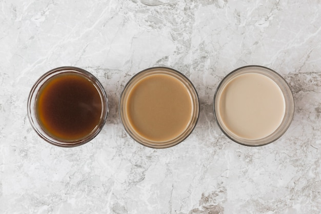 Four coffee cups in a row on marble backdrop displaying different mixtures of milk and coffee