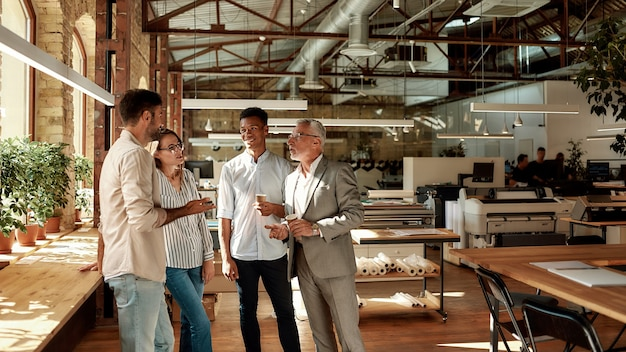 Four colleagues holding coffee cups and talking about something while standing in creative office