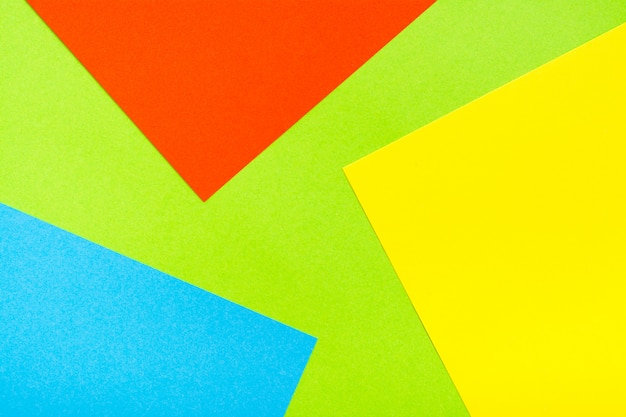 Four-color yellow green red blue abstract cardboard background. sheets of cardboard are stacked on top of each other. copy space