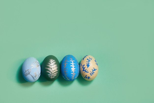 Four colored easter eggs on a green background top view. copy space