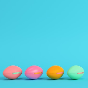 Four colorful american football balls on bright blue background