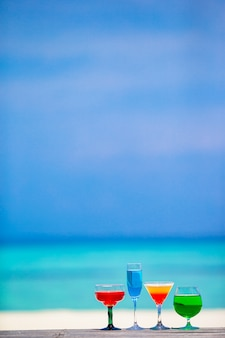 Four colorful exotic tasty cocktails background turquoise sea