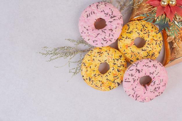 白い表面に4つのカラフルな甘いドーナツ