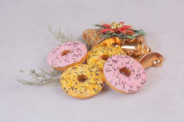 Quattro ciambelle dolci colorate sulla superficie bianca