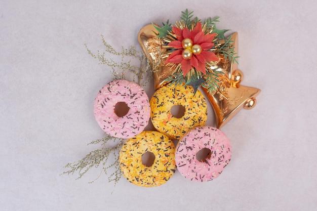 Quattro ciambelle dolci colorate sul tavolo bianco.