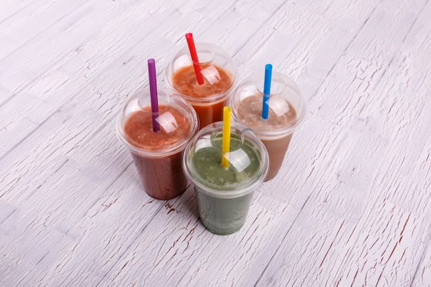 Four colorful, useful and healthy smoothies in plastic cups